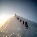 montañeros subiendo la cumbre